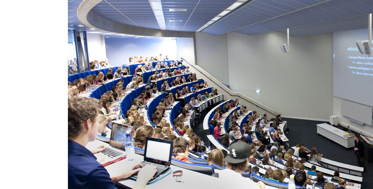 Docent geeft les in blauwe collegezaal